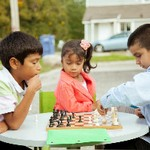 Young girl watches two young boys play chess